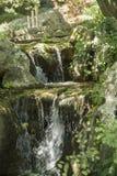 Beautiful waterfall in Japanese garden. Close-up of Japanese garden waterfall with stone bridge in sunlight Stock Photos