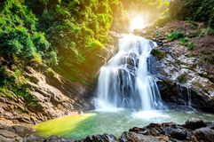 Beautiful waterfall at the mountain with blue sky and white cumulus clouds. Waterfall in tropical green tree forest. Waterfall. Is flowing in jungle. Nature stock images