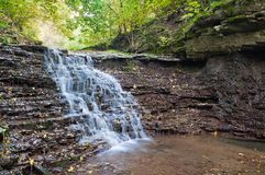 Beautiful waterfall on a mountain stream in the woods Royalty Free Stock Photos