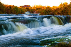 Beautiful waterfall on the rapid river. Among the rocks at sunset. Eastern Ukraine royalty free stock images