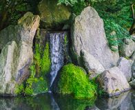 Beautiful waterfall with streaming water with big stones and some covered with green moss peaceful nature scenery background. A beautiful waterfall with stock photos
