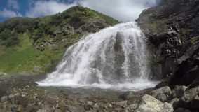 Beautiful waterfall on sunny day. Kamchatka mountain landscape: summer view at the bottom of a beautiful waterfall on a sunny day. Mountain Range Vachkazhets stock video footage