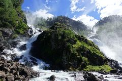 Beautiful Latefossen waterfall with two adventurous goats in Norway royalty free stock images