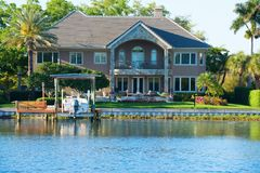 Beautiful waterfront house with artistic stone work with FOR SALE sign in yard Royalty Free Stock Images