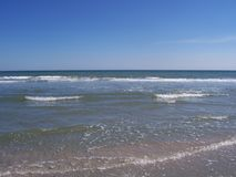 Beach line with beautiful ocean small waves clear sky royalty free stock photo