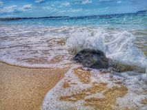 Beautiful wave breaks to the shore and it called swash. Crystal clear water on the shore beach stock image