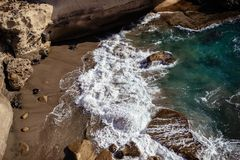 Waves crashing breaking on the rocks. Drone aerial sea surface view stock photography