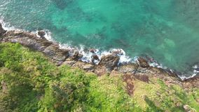 Beautiful waves and sea shore cliff with green palms. Tropical 4K Aerial View. Phuket Island, Thailand.  stock video footage