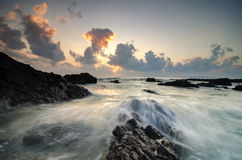 Beautiful waves splashing on unique rocks formation at Pandak Beach located in Terengganu,Malaysia. Over stunning sunrise background.soft focus image due to royalty free stock images