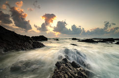 Beautiful waves splashing on unique rocks formation at Pandak Beach located in Terengganu,Malaysia. Over stunning sunrise background.soft focus image due to stock images