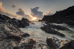 Beautiful waves splashing on unique rocks formation at Pandak Beach located in Terengganu,Malaysia over stunning sunrise. Background.soft focus image due to royalty free stock images