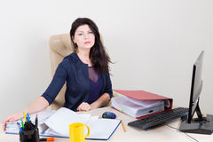 Beautiful weary woman at office working with papers Royalty Free Stock Photography