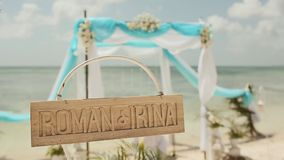 Beautiful wedding arch on the beach. Wooden nameplate with the names of the bride and groom. Wedding day. stock footage