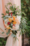 Beautiful wedding arch decorated with peachy cloth and flowers Stock Photos