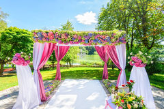 Beautiful wedding arch with flowers in garden Stock Photo