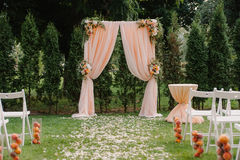 Beautiful wedding archway. Arch decorated with peachy cloth and flowers Stock Photo
