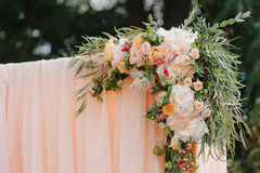 Beautiful wedding archway. Arch decorated with peachy cloth and flowers Stock Photos