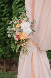 Beautiful wedding archway. Arch decorated with peachy cloth and flowers Royalty Free Stock Photos