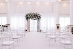 Beautiful wedding archway. Arch decorated with peachy and silvery cloth and flowers. In wedding hall royalty free stock image