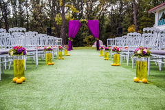 Beautiful wedding archway with chairs on on each side. Beautiful wedding archway. Arch decorated with purple cloth and green petals with lemons. Whote decorated Stock Photo