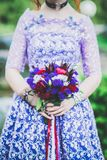 Wedding bouquet in bride`s hands in purple dress Royalty Free Stock Photography