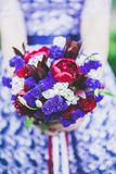 Wedding bouquet in bride`s hands in purple dress Royalty Free Stock Images