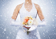 Beautiful wedding bouquet in bride's hands. Winter background with a snowflakes Royalty Free Stock Photo