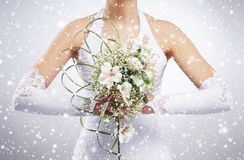 Beautiful wedding bouquet in bride's hands. Winter background with a snowflakes Royalty Free Stock Images