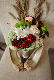Beautiful wedding bouquet and bride's shoes on the coffee table Stock Photos