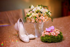 Beautiful wedding bouquet and bride's shoes. Stock Photo