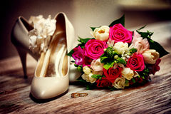 Beautiful wedding bouquet and bride's shoes. Vintage theme background Stock Photography