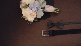 Beautiful wedding bouquet on the chair with bowtie and belt. Beautiful wedding bouquet on the chair with bowtie and black belt stock footage