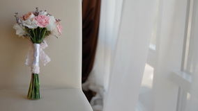 Beautiful wedding bouquet on the chair. Beautiful wedding bouquet of white roses and pink carnations on the chair through the curtains stock video footage