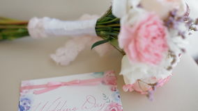 Beautiful wedding bouquet on the chair. Beautiful wedding bouquet of white roses and pink carnations and watercolor invitation card on the chair stock video footage
