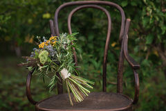 Beautiful wedding bouquet of colorful flowers on a vintage chair on the nature in sunset light, decorations, preparing for the wed Stock Photo