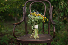 Beautiful wedding bouquet of colorful flowers on a vintage chair on the nature in sunset light, decorations, preparing for the wed Royalty Free Stock Photo
