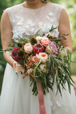 A beautiful wedding bouquet with eucalyptus, roses and exotic flowers in the hands of the bride in a wedding dress. Royalty Free Stock Images