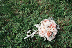 Beautiful wedding bouquet of flowers and ribbons on the green grass. roses. Stock Image