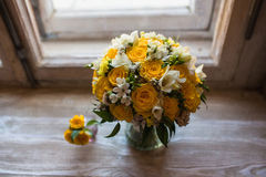 Beautiful wedding bouquet and groom's boutonniere on windowsill background royalty free stock photo