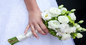 Beautiful wedding bouquet in hands of the bride stock footage