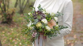 Beautiful wedding bouquet in the hands of the bride in autumn. Slow motion close up stock video footage