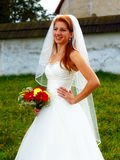 Beautiful wedding bouquet in hands of the bride, and church in background. Stock Photo