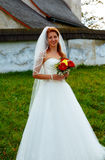Beautiful wedding bouquet in hands of the bride, and church in background. Stock Photography