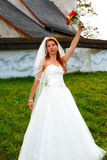 Beautiful wedding bouquet in hands of the bride, and church in background. Royalty Free Stock Photo