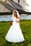 Beautiful wedding bouquet in hands of the bride, and church in background. Stock Image