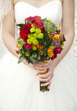Beautiful wedding bouquet in hands of the bride. Beautiful coloured wedding bouquet in hands of the bride Royalty Free Stock Images