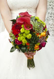 Beautiful wedding bouquet in hands of the bride. Beautiful coloured wedding bouquet in hands of the bride Royalty Free Stock Photo