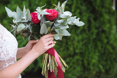 Beautiful wedding bouquet in hands of the bride. Gold ring and white dress Stock Image