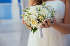 Beautiful wedding bouquet in hands of the bride. Gold ring and white dress Stock Photos