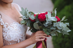 Beautiful wedding bouquet in hands of the bride. Gold ring and white dress Stock Photo